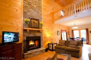 KZ Cabins Star Seasons Retreat Cabin Inside photo of cozy living room with wood burning fireplace
